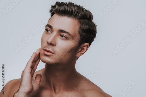 Curious dark haired man looking aside and touching face Fototapeta