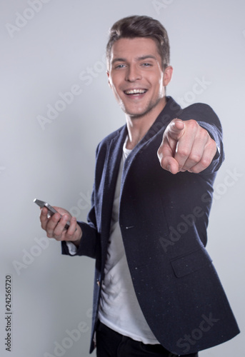 Fotografía  Young cheerful guy smiling looking at smartphone