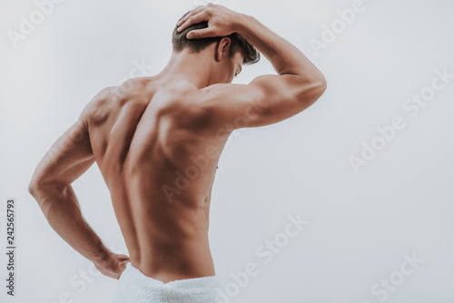 Fotomural  Waist up of man in white towel putting hand on the head