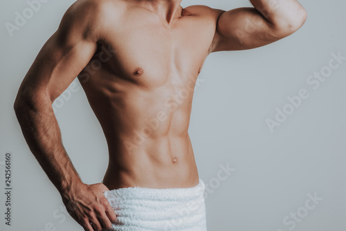 Poster Akt Slim muscular man posing with towel on hips