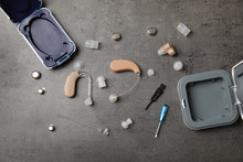 Flat Lay Composition With Hearing Aids And Accessories On Grey Background