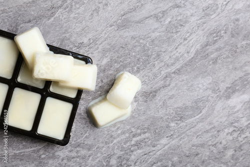 Ice cubes made with milk and tray on grey background, top view. Space for text