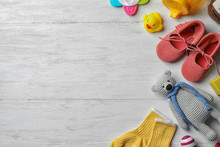 Flat Lay Composition With Baby Accessories And Toys On Light Wooden Background. Space For Text