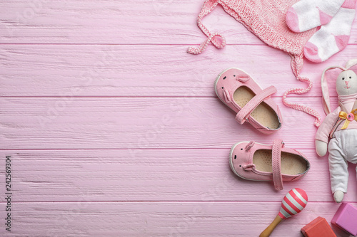 Flat lay composition with baby accessories and toys on color wooden background. Space for text