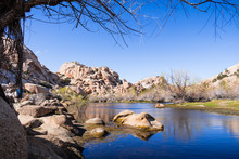 Rock Boulders Reflected In The Calm Waters Of Barker Dam, Joshua Tree National Park, South California