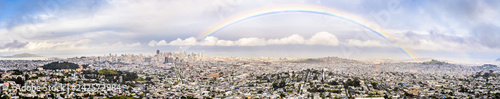 Photo Panoramic view of San Francisco on a rainy day, rainbow stretching above the cit