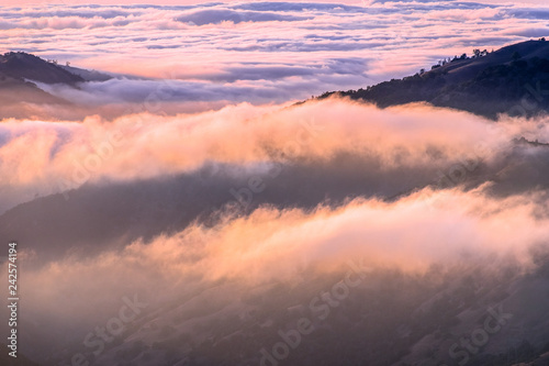 Photo  Clouds bathed in the sunset light covering rolling hills, south San Francisco ba