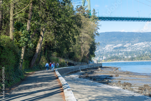 People walking on the Stanley Park Seawall with the Lionsgate Bridge overhead Canvas Print