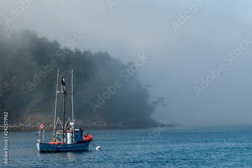 Photo  Fishing boat of Mayne Island flying a Canadian Flag and the Jolly Roger pirate f