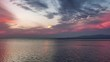Cinemagraph - Beautiful cloudscape and sunset with clouds over sea. Reflection on the water, small ripples.