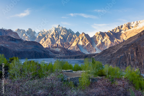 Tuinposter Asia land Tupopdan mountain also known as Passu Cones or Passu Cathedral, big rocks all over the place and blue crystal of Hunza river at sunset time ,Northern of Pakistan