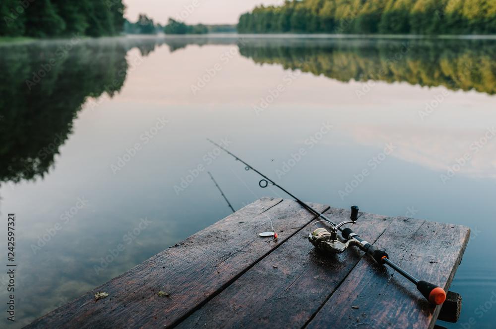 Fototapeta Fishing rod, spoon, hooks on a brown wooden background. fishing bait. close up. throw-line. fishing rod. Rod on the bridge. Bridge passes through the lake, river. flat lay. top view.
