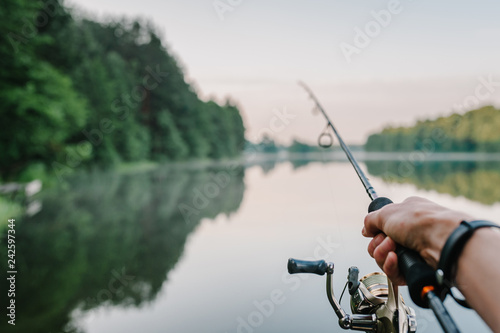 Fotografie, Obraz  Fisherman with rod, spinning reel on the river bank
