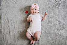 Little Girl Baby Playing With Toys, The Baby Lies On Warm Gray Plaid, Infant Lying On The Background Of A Soft Blanket, Holds The Toy And Smiles. Flat Lay, Top View. Copy Space For Slogan Or Text.