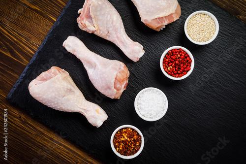 Raw chicken drumsticks on wooden background