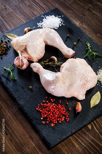 Raw chicken legs on wooden background