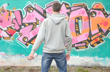 Fototapeta Młodzieżowe - A young graffiti artist in a gray hoodie looks at the wall with
