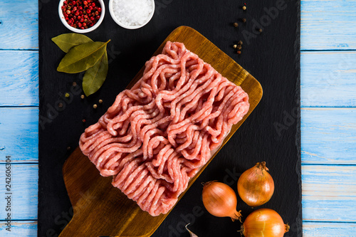 Raw minced pork on cutting board and vegetables