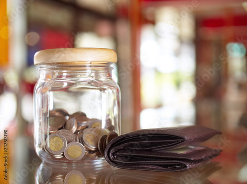 Poster de jardin Bar Glass bottle jar contain lot of coins money saving on mirror table with big wallet black