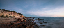 Panoramic Long Exposure Shot Of Red Bluff Lookout, A Burnt Orange-colour Cliff,  Characterised By The Oxidised Iron In The Cliffs With A Rocky Beach In The Sunset Time