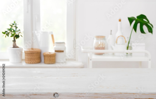 Wooden table on blurred background of kitchen window with utensils Canvas
