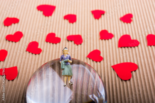 Fotografie, Obraz  Woman figurine on half a globe with paper hearts