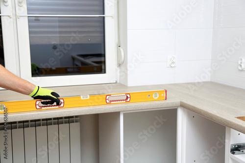 Obraz Pracownik wykonuje pomiary mebli poziomicą. - fototapety do salonu
