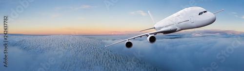 Huge two-storey passengers commercial airplane flying above dramatic clouds, sunset.