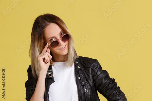 Fotografie, Obraz  Playful young blonde girl took off her sunglasses and looks into the camera posing on a yellow background