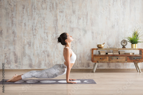 Poster Ecole de Yoga Young indian girl doing yoga fitness exercise indoor. Wellness concept. Calmness and relax. Yogi Instructor doing Urdhva mukha shvanasana exercise, upward facing dog pose, working out, home interior