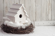 Easter. White Eggs On Wooden Table With Feathers, Branches And Birdhouse