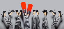 Standing Out From Others Concept. Female Sexy Legs Wearing High Heels And One Woman Wears Red Flippers Isolated Over Gray Background