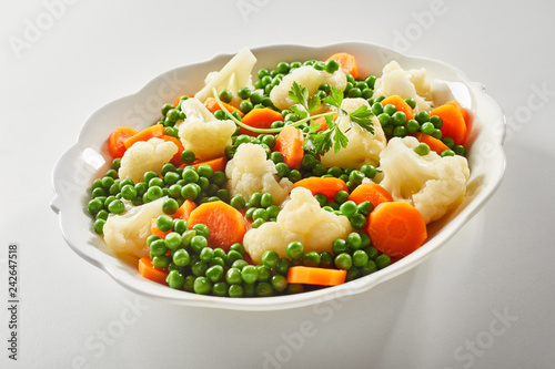 Photo Ceramic bowl of tender steamed mixed vegetables