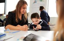 Young Female Teacher Working W...