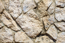 White Stoned Wall In Uneven Cut For Background. Closeup View Of Chalky Dry Rock Formation In Abstract. Crazy Pattern Of Rock Paved Structure Art Of Masonry