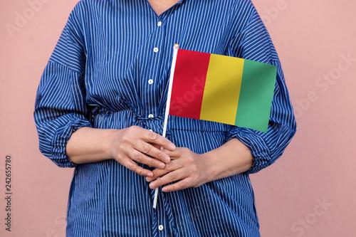 Fotografía  Guinea flag. Close up of woman's hands holding Guinea flag.