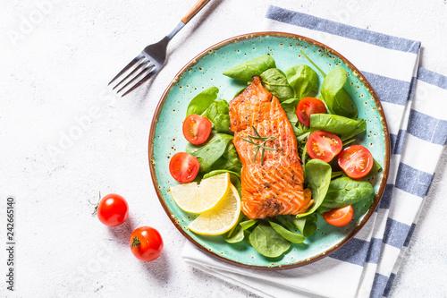 Fotografija Baked salmon fish fillet with fresh salad top view on white.