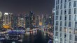 Luxury Dubai Marina canal with passing boats and promenade night timelapse, Dubai, United Arab Emirates