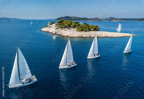 Amazing view of racing sailing boat with small island and crystal clear water