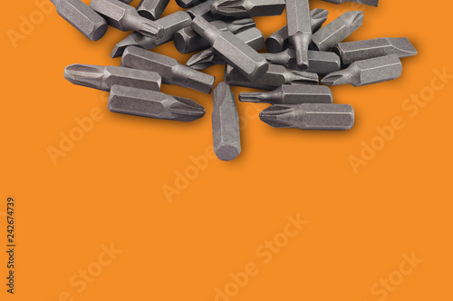 Fotografie, Obraz  One heap of different interchangeable heads or bits for manual screwdriver for woodworking and metalworking on orange background with copy space for your text