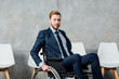 handsome businessman sitting in wheelchair in waiting hall and looking at camera