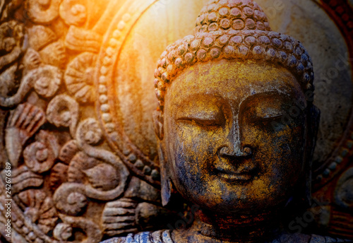 Stampa su Tela  Rock Buddha statue with sunlight used for amulets of Buddhism religion