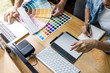 Team of young colleagues creative graphic designer working on color selection and drawing on graphics tablet at workplace, Color swatch samples chart for selection coloring