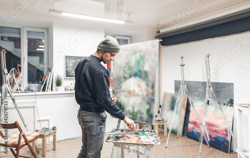 Portrait of an artist's student, drawing a painting in a studio. Young painter paints a new oil painting in his own cozy studio. Creative work.