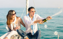 Young Couple In Love On Sailing Boat Cheering With Champagne Wine Bottle - Happy Girlfriend Birthday Party Cruise Travel On Luxury Sailboat - Focus On Boyfriend Face With Sunny Afternoon Color Tones