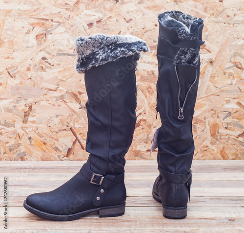 Fotografía  Tall boots with fur lining at wood background