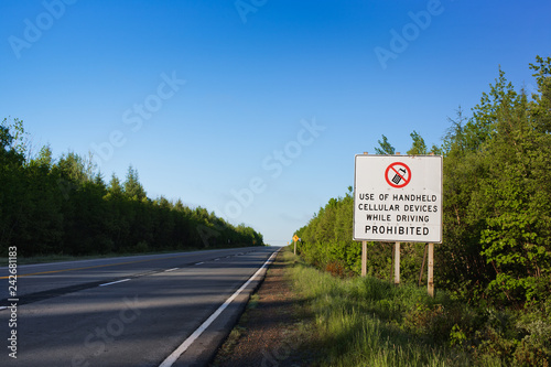 Fotografía  Highway sign prohibiting use of handheld cellular devices while driving