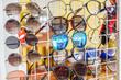 Many different color sunglasses. Brilliant mirror multicolor sunglasses. A market tray with multicolor sunglasses, Sale of cheap glasses on the street.