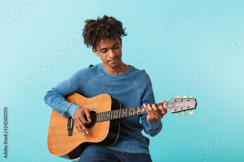 Obraz na plátne Handsome young african man playing a guitar