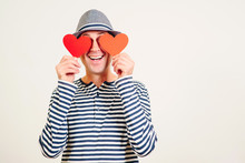 Happy Valentine Day. Man In Love. Boyfriend Holding Heart Shaped Valentine Cards In Front Of His Eyes. Blinded By Love. Hipster In Hat With Valentine Cards, Isolated On White. Copy Space. Love Mood.